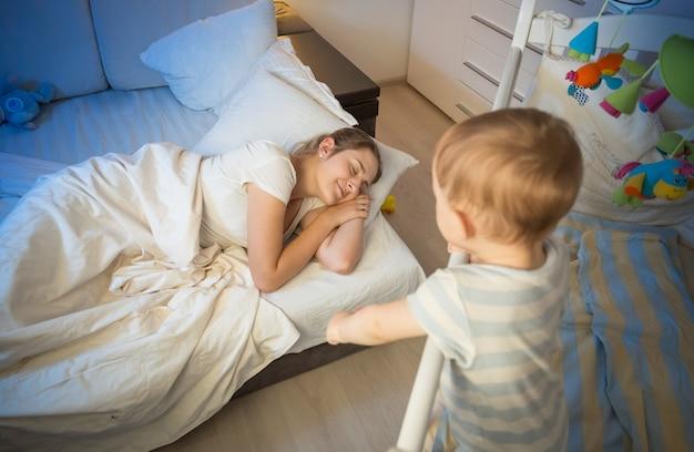 Bebê no berço tentando acordar a mãe que adormeceu Foto Premium