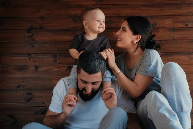 Bebê nos ombros de seu pai e brincando com a mãe.