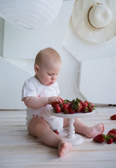 Bebê ocupado sentado no chão comendo morangos em uma superfície branca com espaço para texto
