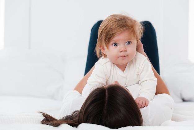 Bebê olhando para longe realizada pela mãe