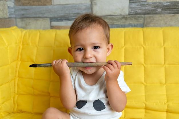 Bebê olhando seriamente para a câmera e mordendo pincéis; ele está com os dentes começando a babar