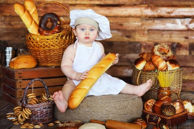 Bebê padeiro com chapéu e avental de chef segurando uma baguete francesa ou pão no fundo de uma padaria e produtos de padaria