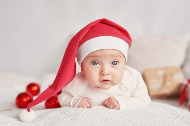 Bebê papai noel com decoração de ano novo em uma luz