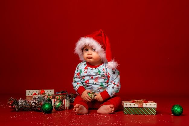 Bebê papai noel em fundo vermelho, espaço para texto
