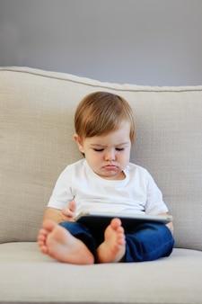 Bebé pequeno bonito com expressão engraçada da cara que olha desenhos animados na tabuleta digital
