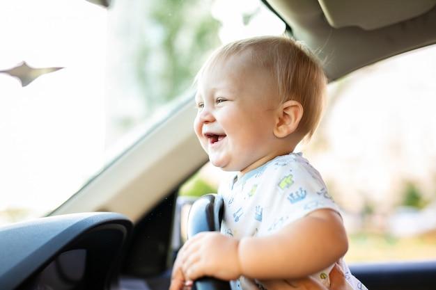 Bebé pequeno bonito que conduz o carro grande, guardando o volante, sorrindo e olhando para a frente com interesse.