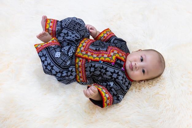 Bebê pequeno bonito que dorme no tapete de seda macio macio com vestir um traje tradicional.
