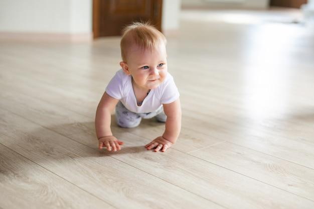 Bebé pequeno bonito que encontra-se na folhosa e no sorriso. criança rastejando sobre parquet de madeira.