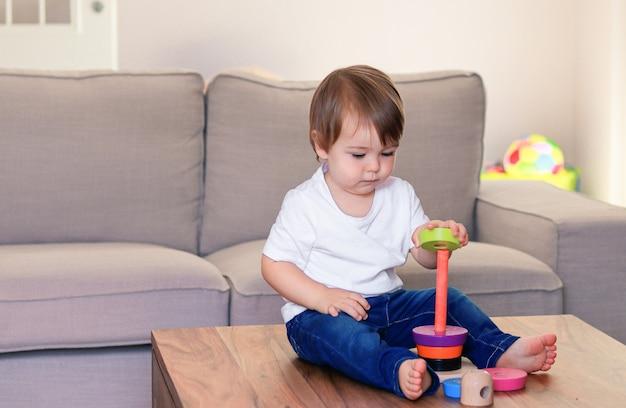 Bebé pequeno bonito que joga com pirâmide de madeira colorida em casa.