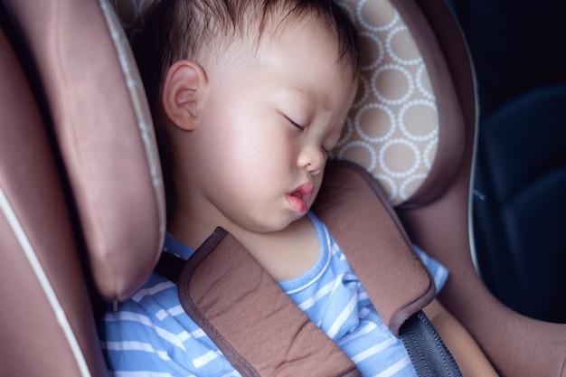 Bebé pequeno e fofinho asiático de 1 ano, menino, dormindo em uma cadeirinha de carro moderna