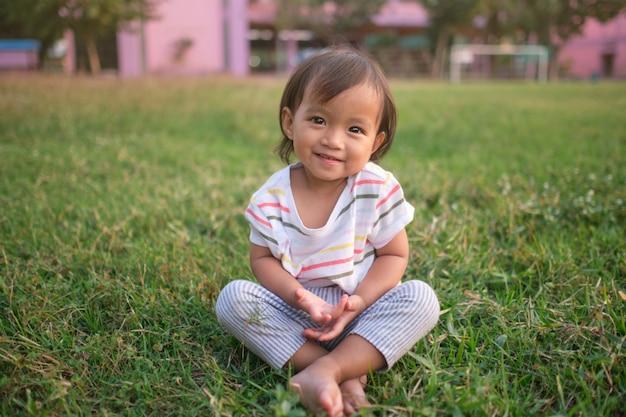 Bebé pequeno e fofo asiático de 1 a 2 anos de idade, menina, sorrindo para a câmera, praticando ioga descalça e meditando ao ar livre
