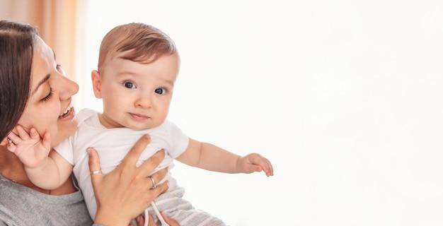 Bebê pequeno encantador com mãe em casa, close-up retrato sincero