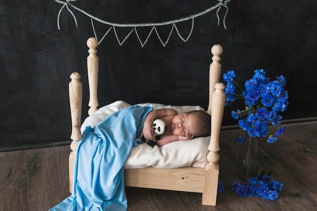 Bebê pequeno exigente dormindo na cama pequena