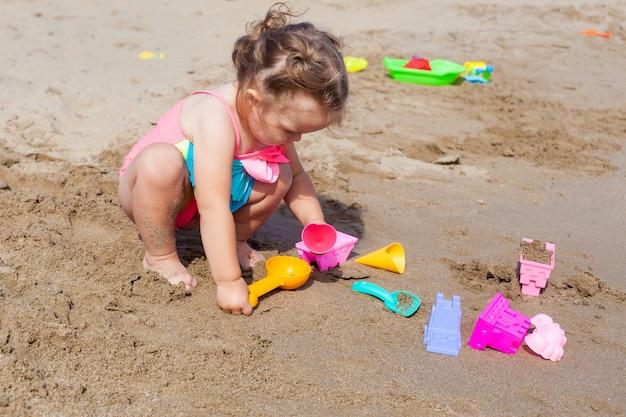 Bebé pequeno feliz no roupa de banho que joga na areia na praia em um dia morno ensolarado.