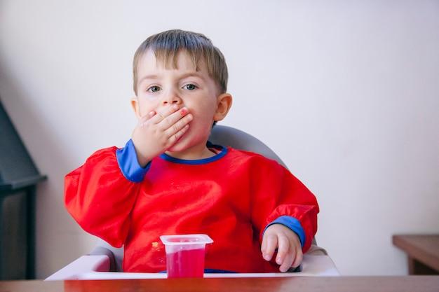 Bebê pequeno que come a sobremesa doce em uma maneira desarrumado. estilo de vida familiar e dieta saudável.