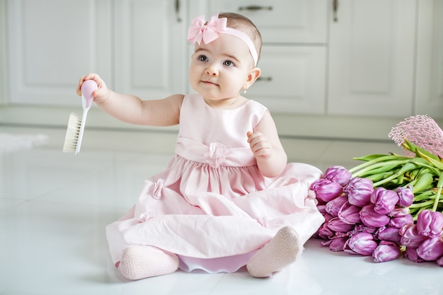 Bebê pequeno que guarda o cabelo do pente o conceito de infância