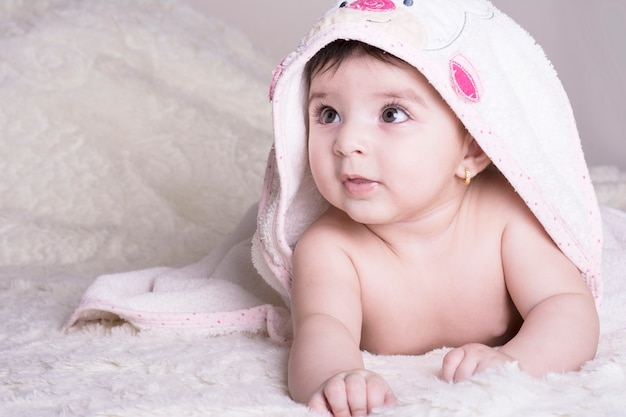 Bebê pequeno que veste a toalha de banho branca, relaxando no cobertor inchado branco