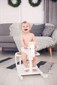 Bebê pequeno sorridente, jogando em um cavalo de madeira do brinquedo na sala aconchegante.