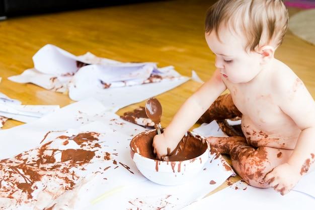 Bebê pintando com as mãos com chocolate