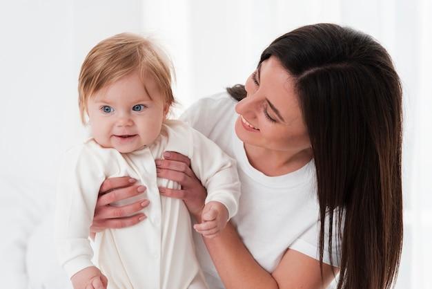Bebê posando enquanto segura pela mãe