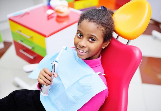 Bebé preto bonito que sorri sentando-se em uma cadeira dental vermelha no exame no dentista das crianças