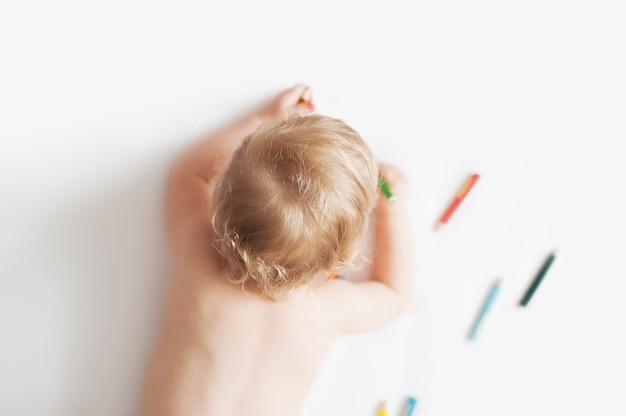 Bebé que desenha com os lápis coloridos no fundo branco