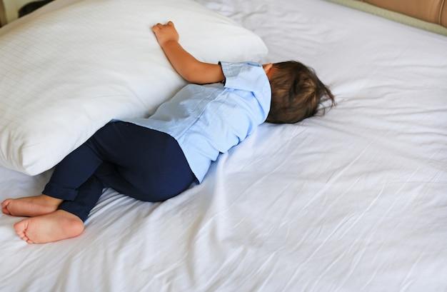 Bebé que dorme na cama com aperto de um descanso. visão traseira.