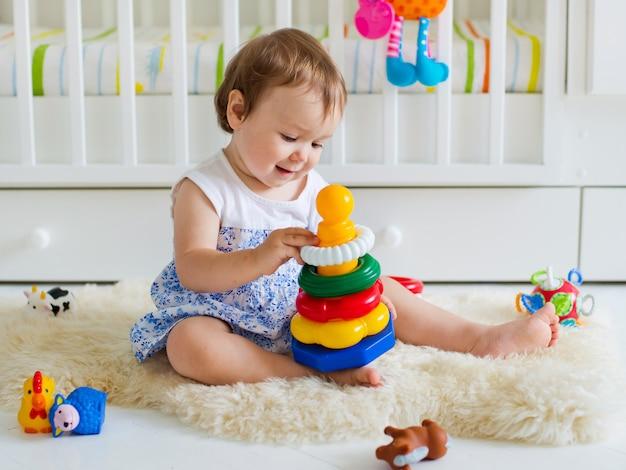Bebé que joga com o brinquedo educacional no berçário