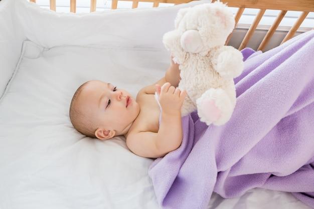Bebé que joga com um brinquedo macio em um berço