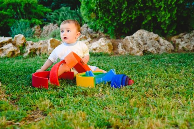 Bebé que joga com um material de waldorf, um arco-íris do montessori de madeira, na natureza.