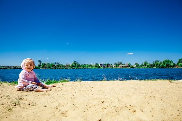 Bebé que senta-se na praia e que joga com areia