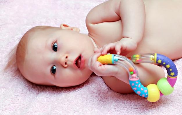 Bebê recém-nascido brincando com chocalho colorido
