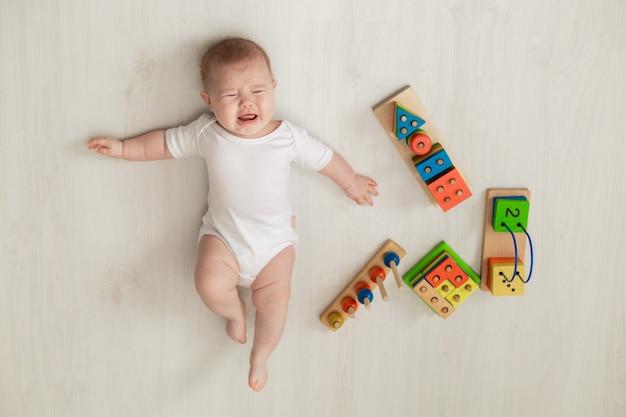 Bebê recém-nascido chorando em um macacão branco deita-se de costas no chão e brinca com brinquedos educativos