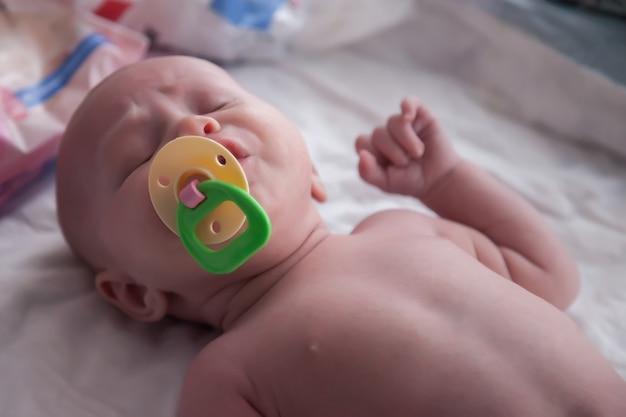 Bebê recém-nascido com chupeta colorida na cama branca
