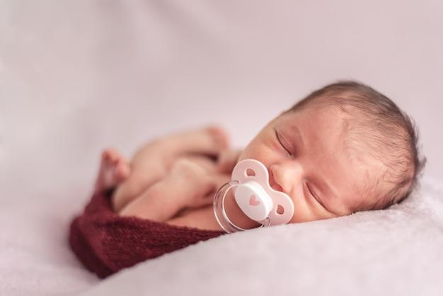Bebê recém-nascido com chupeta dobrada em uma bola de lã