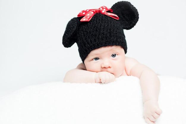 Bebê recém-nascido com um chapéu na cabeça, deitado no cobertor sorrindo, uma linda menina recém-nascida