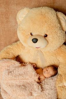 Bebê recém-nascido de duas semanas dormindo no ursinho de pelúcia.