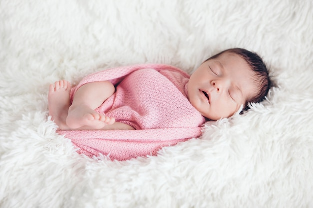 Bebê recém-nascido dorme envolto em um cobertor.