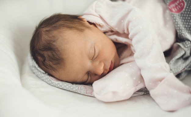 Bebê recém-nascido dormindo bem, vestindo roupas quentes e deitado em um sofá de bebê