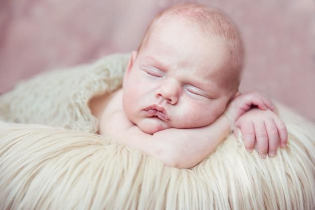 Bebê recém-nascido dormindo com as mãos atrás da cabeça