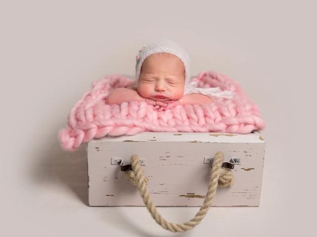 Bebê recém-nascido dormindo com bochechas gordinhas deitado na caixa no tapete