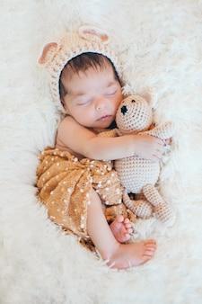 Bebê recém-nascido dormindo com um brinquedo ao lado do urso de pelúcia de malha
