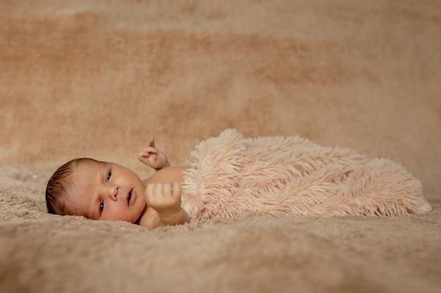 Bebê recém-nascido dormindo, descansando nas próprias mãos e cotovelos
