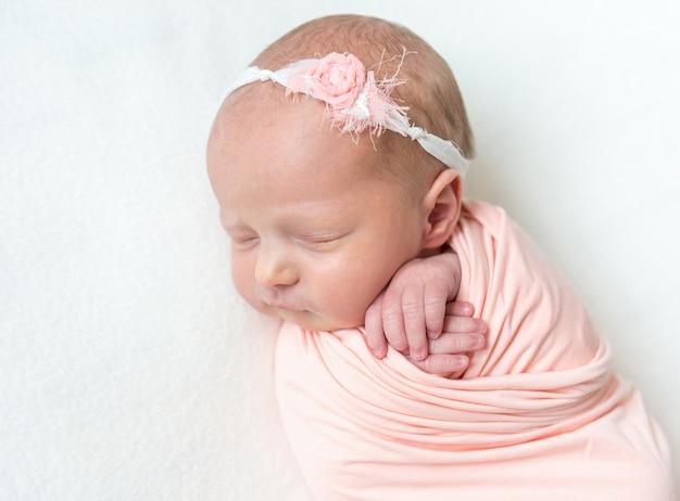 Bebê recém-nascido dormindo em um envoltório rosa