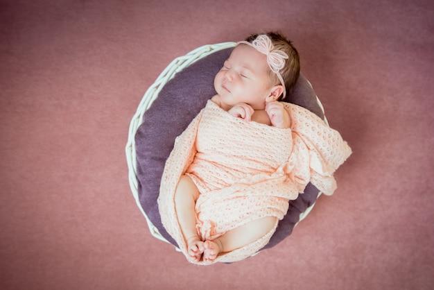 Bebê recém-nascido dormindo em uma cesta em um cobertor rosa