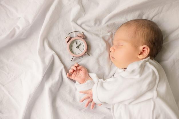 Bebê recém-nascido dormindo enrolado em um cobertor branco