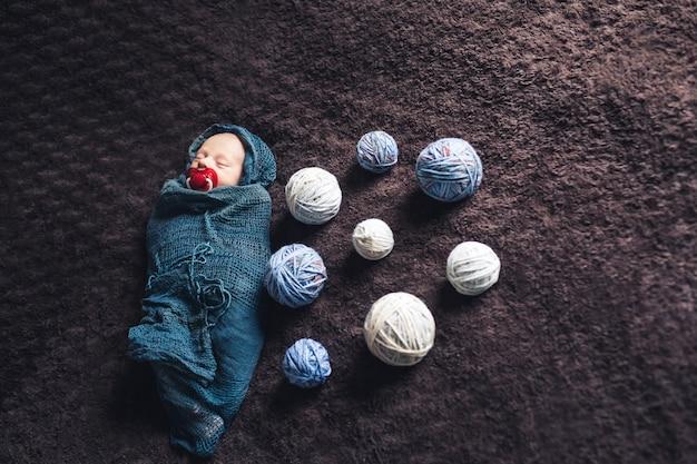 Bebê recém-nascido dormindo enrolado em um cobertor em meio a emaranhados de linha