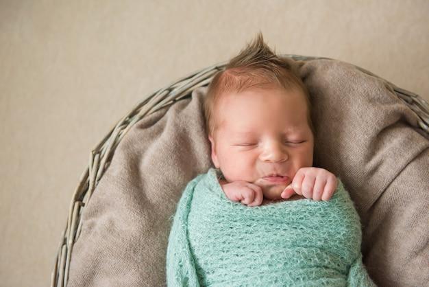 Bebê recém-nascido dormindo na cesta. cabelo engraçado
