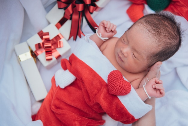 Bebê recém-nascido dormindo na mão da mãe no chapéu de natal com caixa de presente do papai noel