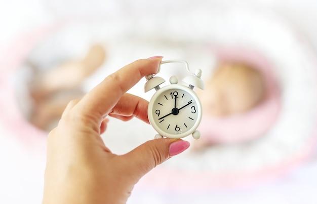 Bebê recém-nascido e despertador. foco seletivo. pessoas.